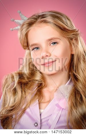 Portrait of a pretty little girl with beautiful blonde hair over pink background. Little princess with a crown on her head. Kids fashion.