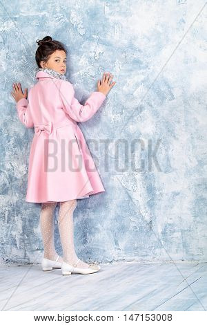 Elegant eight-year girl in pink coat. Kid's fashion.