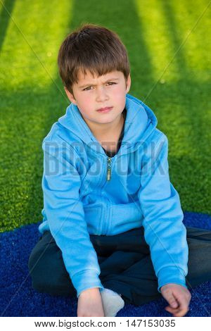 Playground in winter sunny day. Beautiful six year old boy posing on artificial turf
