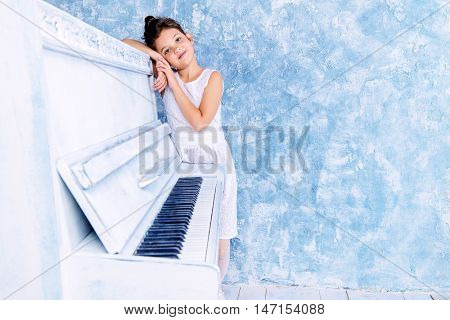 Elegant eight-year girl in white dress playing the piano. Music and art concept. Retro, vintage style.