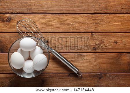 From above on glass bowl full of whole eggs and wire whisk on rustic board with copyspace