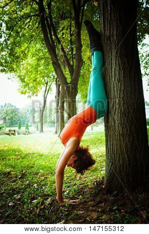 young woman practice yoga  in park handstand next tree