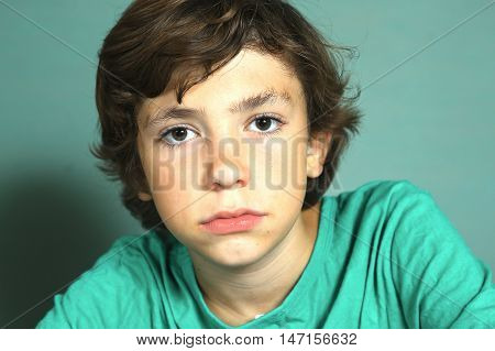 preteen handsome boy close up portrait on blue wall background