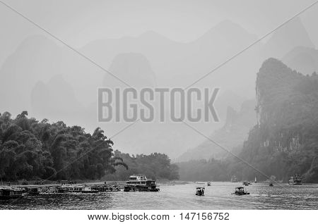 Cruise ship and boats packed with tourists travels the magnificent scenic route in the haze along the Li river from Guilin to Yangshou - black and white photography.