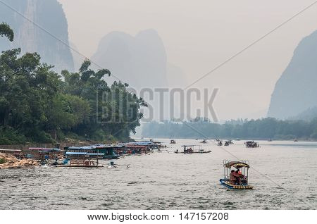 Xingping China - October 20 2013: A tourist boats travels the magnificent scenic route along the Li river from Guilin to Yangshou in the haze.