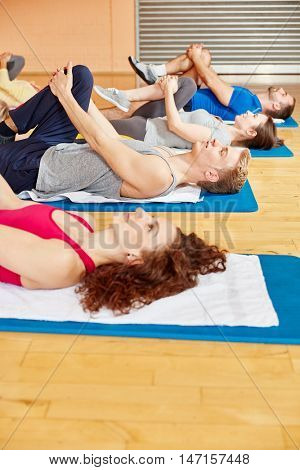 Group of people stretching in pilates class at fitness studio