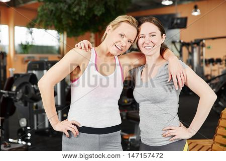 Happy sporty couple of women as friends at the gym hughing each other