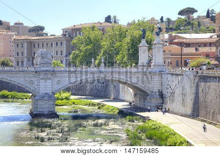 Old stone bridge of Vittorio Emanuele II across the river Tiber in the historical center of city Rome