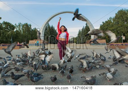 Girl in red jacket listening to music streaming with headphones and dancing on the street among the flying pigeons.