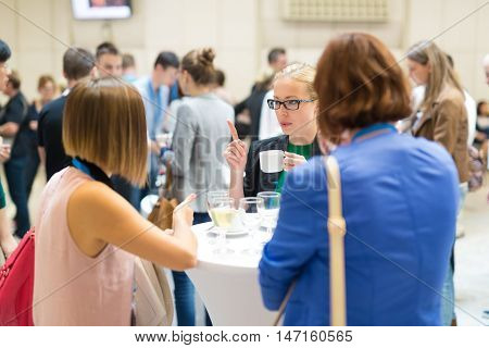 People interacting during coffee break at medical or scientific conference.