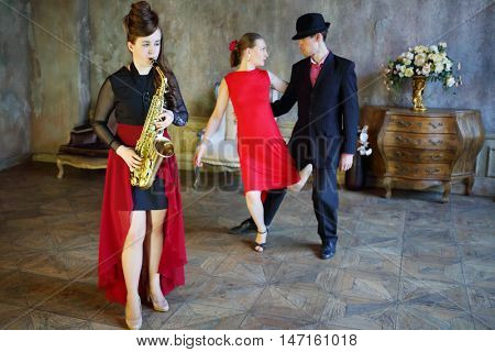 Couple dancing tango near girl playing saxophone. Pair out of focus