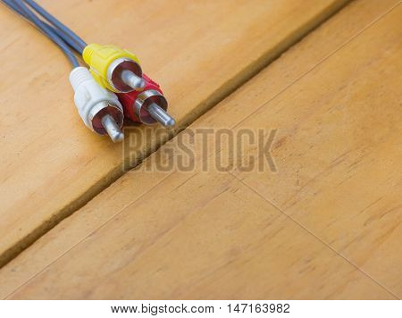 audio input equipment on wood background;audio jack soft focus;Mini jack closeup with cable and earbuds in the background