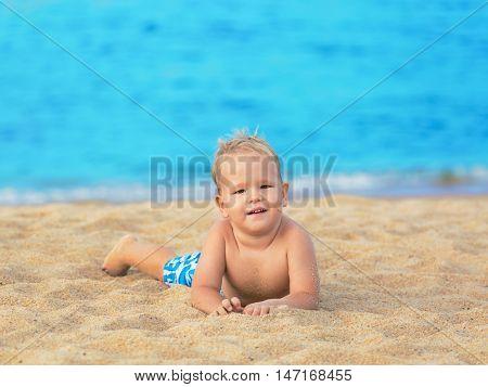 Cute boy relaxing on the tropical beach