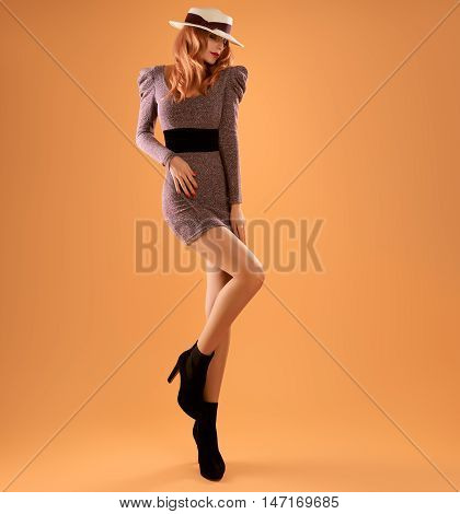 Fall Fashion. Model Woman in Autumn fashion Outfit. Stylish Dress Trendy Hat Fashion autumn shoes. Glamour Playful Redhead Sexy girl Long Legs. Fashion Pose. Fall Concept. Creative Vintage Retro Pinup
