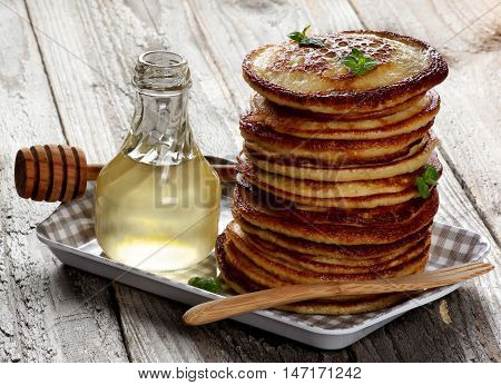 Stack of Delicious Homemade Pancakes with Mint Leafs Honey in Glass Container and Honey Dipper in Checkered Tray closeup on Wooden background