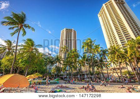 Waikiki, Oahu, Hawaii - August 18, 2016: tourist sunbathing on Waikiki beach at sunset. Waikiki beach, South Shore, is neighborhood of Honolulu and the most popular of Hawai.
