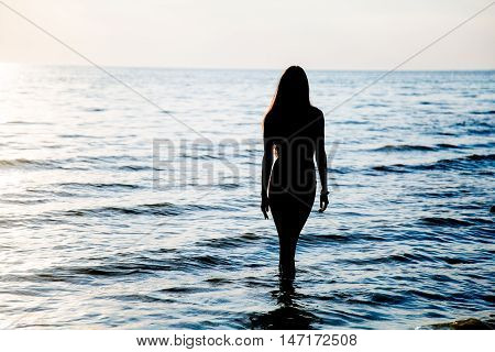 Young Beautiful Woman Walking On The Water On The Beach At Sunset In Swimsuit