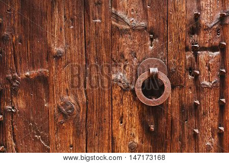 Old wooden door with bright texture on Mallorca, Spain. Metal hand, old knocker.