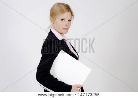 Young freckled businesswoman is standing with a portfolio, looking into the camera with an elegance smile. Studio shot with light background. Isolated.