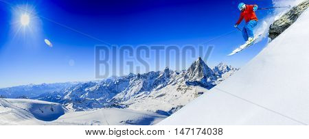 Skier skiing downhill in high jumping from the rocks mountains in fresh powder snow. Snow mountain range with Matterhorn in background. Zermatt Alps region Switzerland