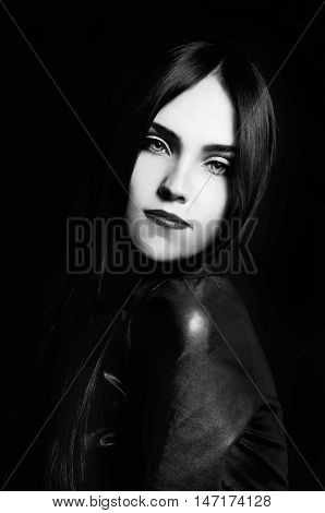 Gorgeous brunette with white skin red lips long black hair transparent eyes on black backdrop looking mysterious and sexy. Black and white.
