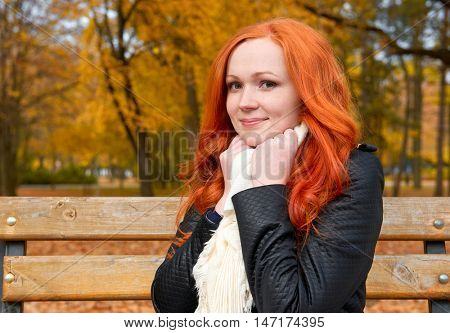 beautiful young girl portrait sit on bench in park, yellow leaves at fall season, redhead, long hair