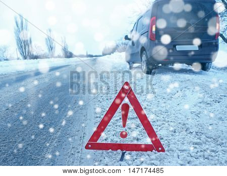 Warning triangle with car breakdown on background. Winter road safety concept.