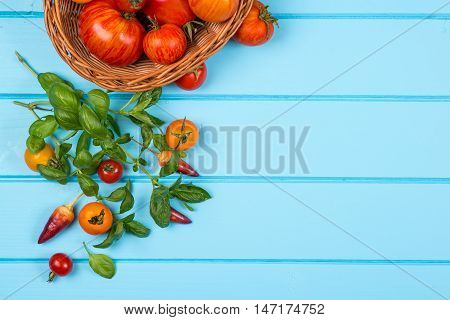 Vegetable background. Fresh peppers tomatoes basil on the blue wooden background.