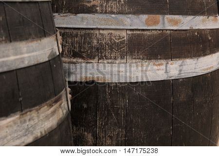 Close Up Of Old Worn Oak Wooden Barrels With Rusty Iron Bands