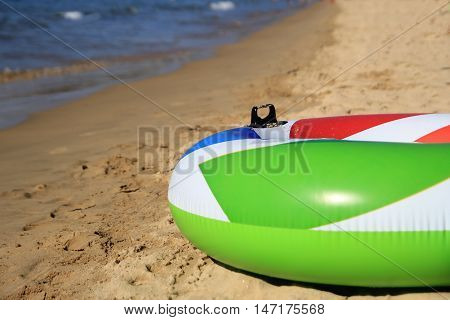 Colorful Inflatable Ring On A Beautiful Sandy Beach In The Summer Sunshine, Green, Red, White, Blue.