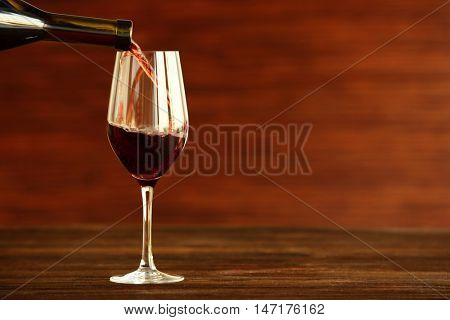 Red wine pouring into a glass on wooden background