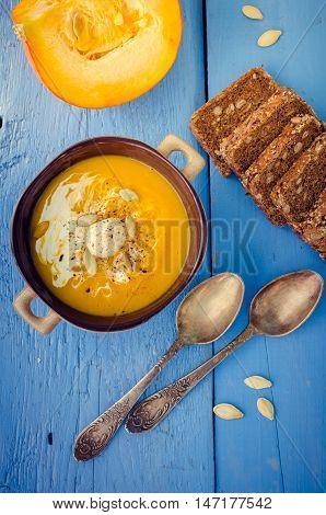 Pumpkin soup with cream cheese and pumpkin seeds on blue wooden background. Pumpkin soup with fresh pumpkins. Halloween Thanksgiving Autumn food concept. Top view.
