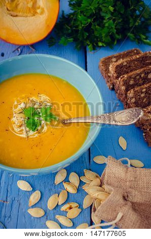 Pumpkin soup with cream cheese and pumpkin seeds on blue wooden background. Pumpkin soup with fresh pumpkins. Halloween Thanksgiving Autumn food concept. Selective focus.