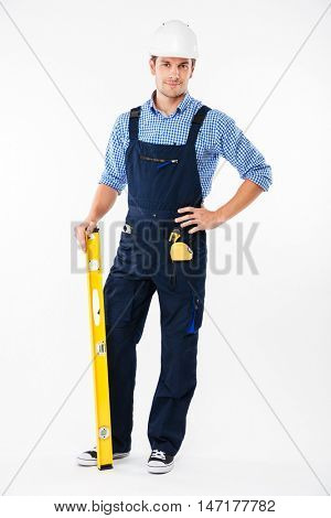 Full length portrait of a smiling male builder standing isolated on a white background