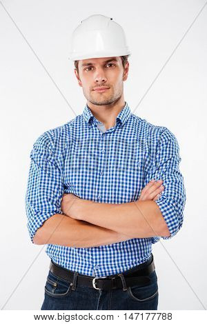 Serious handsome young man architect in building helmet standing with arms crossed over white background