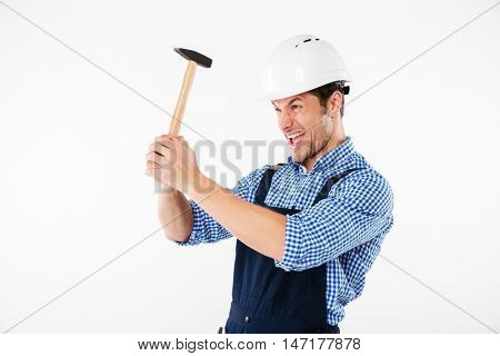 Funny young builder applying hummer to his head in helmet and having fun isolated on a white background