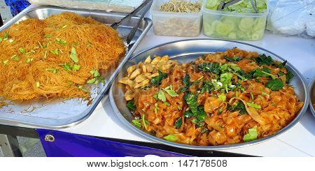 Southern Thai spicy pasta and noodles, with fresh sprouts, cucumbers, and greens on metal platters, for sale in Ranot, Thailand