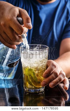 Bartender pours soda water in mojito cocktail