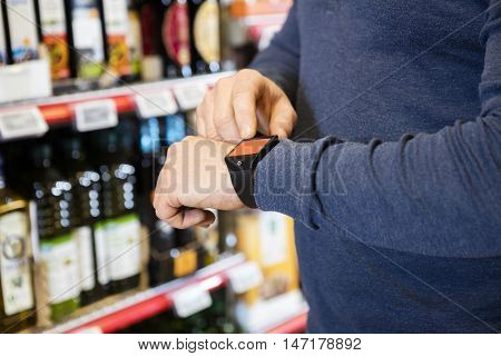 Midsection Of Customer Touching Smartwatch's Screen In Grocery