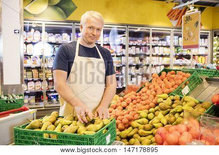 Confident Salesman Arranging Fresh Pears In Supermarket