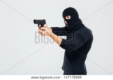 Criminal man in balaclava standing and aiming with gun