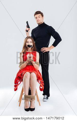 Theatrical scene with man murderer with gun and scared tied woman victim isolated on the white background