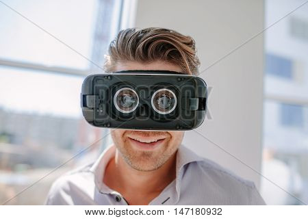 Close up of happy young man wearing virtual reality goggle. Male with VR headset connecting device.