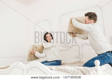Happy Couple Having Pillow Fight in White Hotel Room.