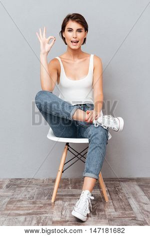 Attractive brunette woman sitting on the chair and showing okay sign over gray background