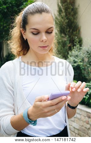 Young Woman In Business Clothes Walking Down The Street And Using A Mobile Phone With Touch Screen