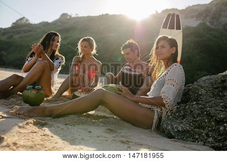 Group of young friends partying on the beach. Young people having fun at beach party with man playing dumbek.