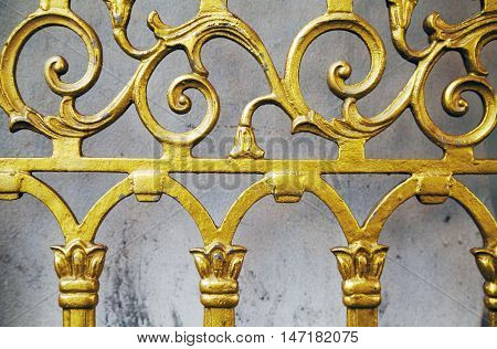 Gold old wrought fence close-up background. Forged ornate beautiful pattern golden gate at shrine