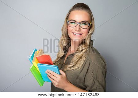 Portrait of a nice happy student girl wearing glasses reading book in the studio over gray background, gain knowledge in the college