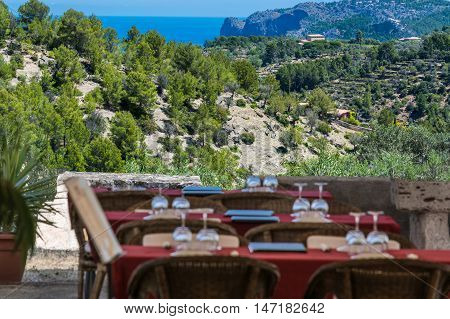 Focus on background. Tables and chairs of a romantic secretive restaurant on the coast of the island of Mallorca Spain.